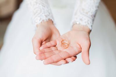 Alianzas de oro amarillo sostenidas por las manos de una novia
