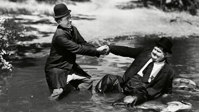 Stan helps Ollie out of a hole in Way Out West