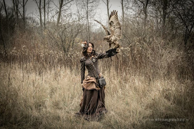 Woman in steampunk victorian clothing in shades of brown, in a field with a falcon