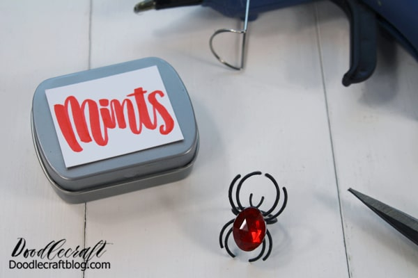 """Step 1: Trick Spider Tin Begin by adhering the magnet to the backside of the tin. Then place the """"mints"""" label on the front of the tin if needed."""