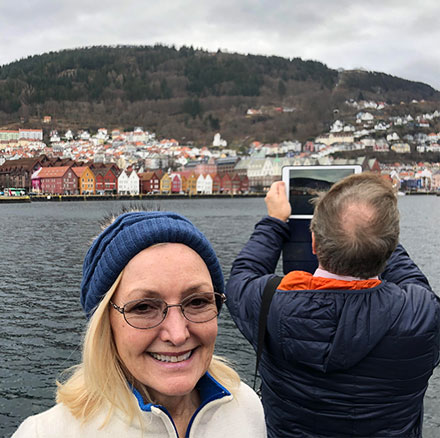 Resident Astronomer Peggy poses with iconic Bergen houses in the background (Source: Palmia Observatory)