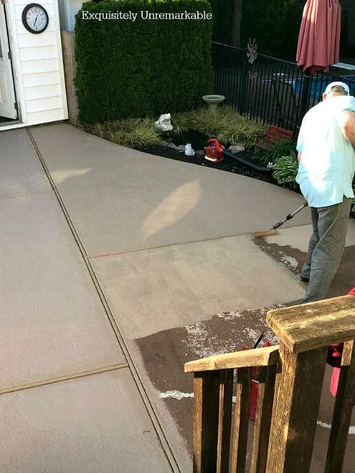 A man painting a cement patio with a roller.