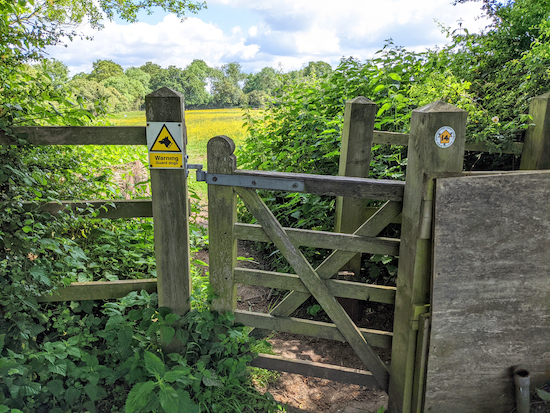 A 'Warning Guard Dogs' sign on the gate halfway along footpath 14