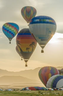 Cramer Imaging's fine art photograph of a hot air balloon cluster taking flight in Panguitch Utah with a sunburst off 1 aerial balloon