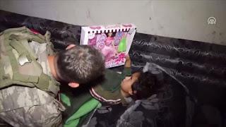 جنود أتراك يطمئنون على صحة طفلة سورية بتل أبيض(فيديو)