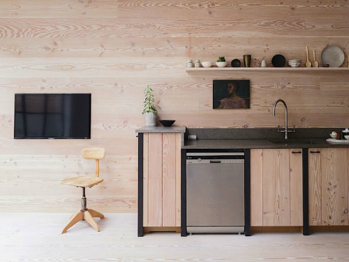 Die Schränke sind aus Holz kombiniert mit schwarzen Stahlstreben und einer grauen Beton-Arbeitsplatte.