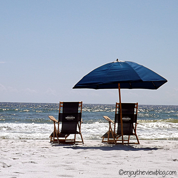 two blue chairs and umbrella on the sand at the seashore