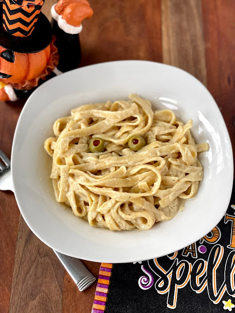 The alfredo coated pasta in a bowl with olive eyes.