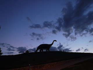 the silhouette of a huge concrete brachiosaurus sits against a darkening sky in Rapid City, South Dakota