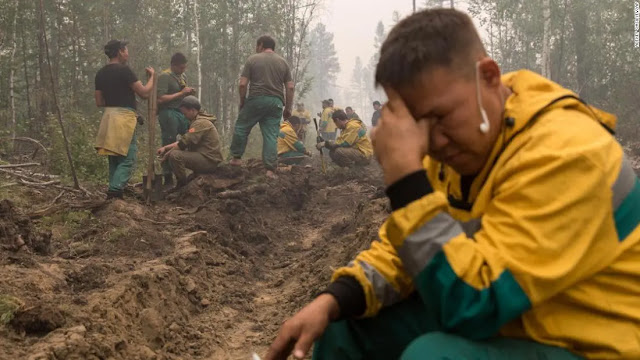 An employee of the Yakutlesresurs forest protection agency in Yakutia rests after digging a trench to prevent a fire. Photo AP