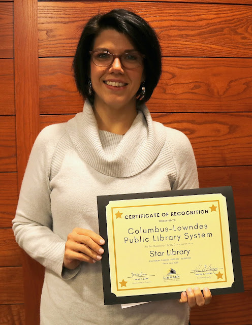 smiling woman holds a certificate of recognition for columbus lowndes public library system