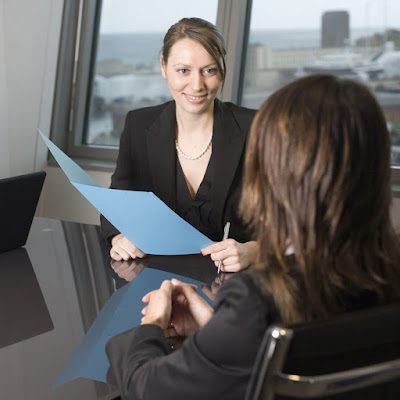 A woman interviewer sits with a folder across from the job candidate