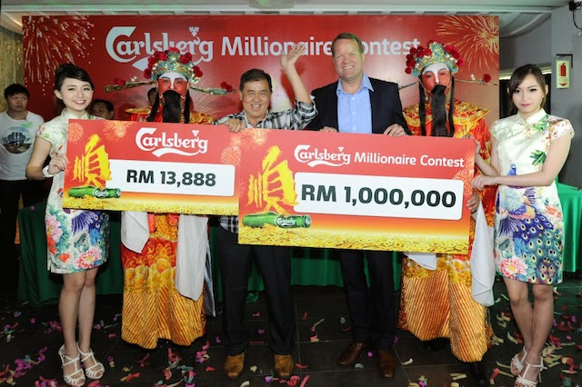 Newly crowned Carlsberg Millionaire, Lim Chong Boon [third from left] waves happily as he is presented with his million dollar cheque by Henrik Juel Andersen, Managing Director of Carlsberg Malaysia [third from right]