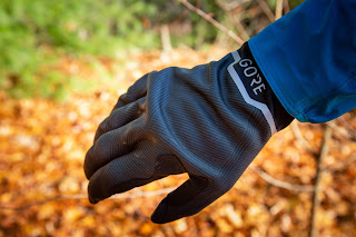 Close up view of the back of the black Stretch Mid Gloves worn on the hand, shown against a blurred background of orange leaves on the ground.