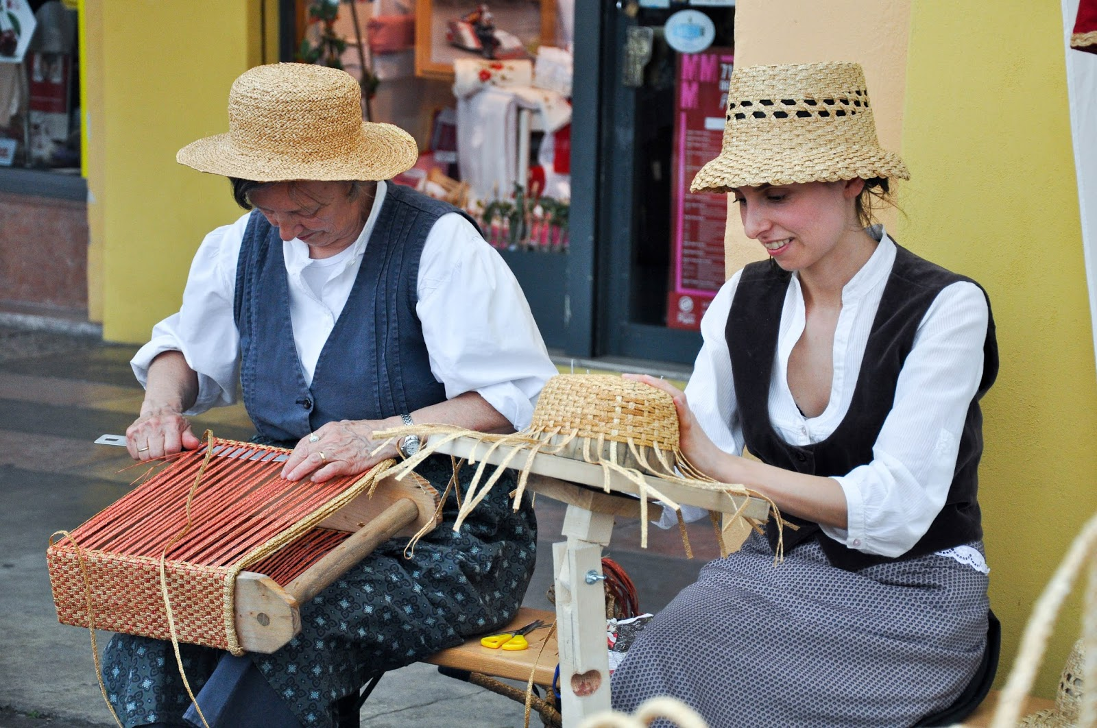 Two ladies weave a bag and a hat, Cherry Show Market, Marostica, Veneto, Italy