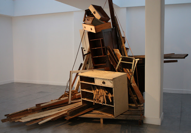 A high sculptural installation consisting of lots of wood and furniture, held together by rope