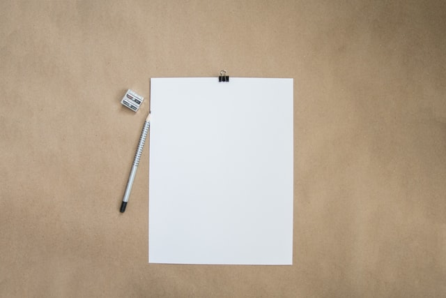 A stock image of a white piece of paper, pencil and pencil sharpener