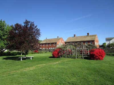 Green lawn, blue sky, and a pair of two-story brick buildings. There are trees and two bright red azalea bushes.