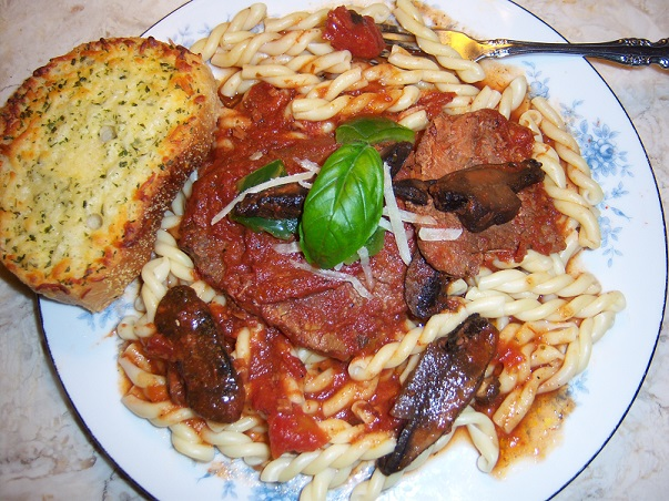 This is a dish of gemelli pasta with round steak and garlic bread