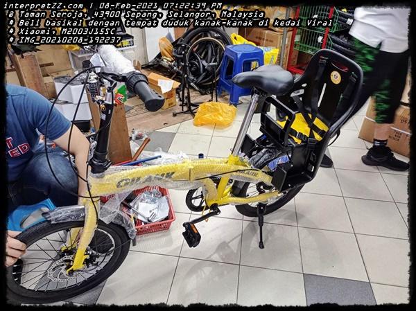 Gambar basikal lipat berjenama Gilank berwarna kuning sedang dipasang tempat duduk untuk kanak-kanak.