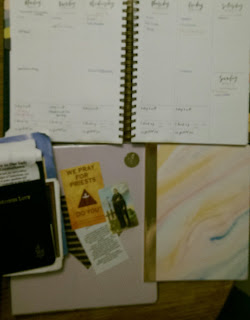 Open planner with prayer books and notebook