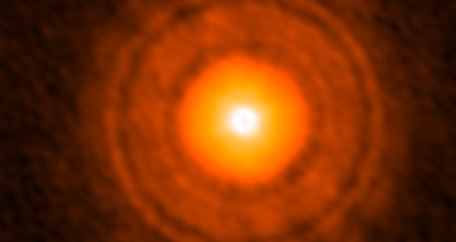 ALMA image of the disk around the young star TW Hydrae. Several gaps are clearly depicted. Researchers found that the size of the dust particles in the inner 22 au gap is smaller than in the other bright regions and guess that a planet similar to Neptune is located in this gap. Credit: ALMA (ESO/NAOJ/NRAO), Tsukagoshi et al.
