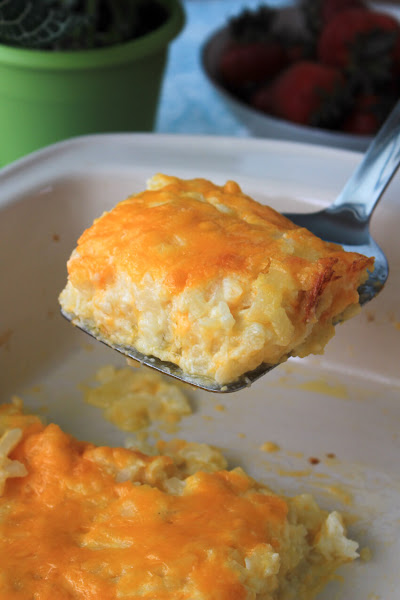 A side view of a spatula serving a sqaure of hash brown casserole.