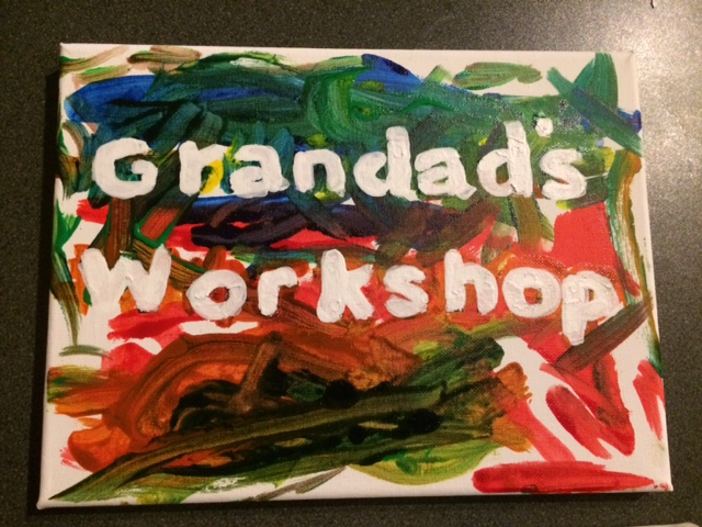 A canvas painted by a child that says granddads workshop