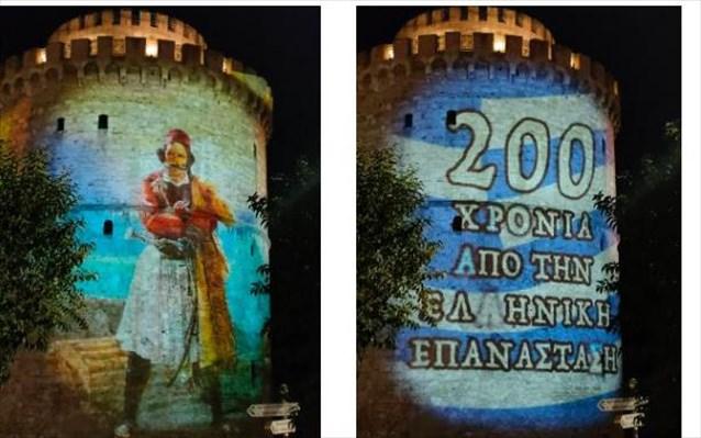 """Στα χρώματα της Ελλάδας και με τα μηνύματα της Ελληνικής Επανάστασης φωτίστηκε απόψε, παρουσία του Δημάρχου Θεσσαλονίκης Κωνσταντίνου Ζέρβα, ο Λευκός Πύργος, στο πλαίσιο σειράς συμβολικών δράσεων που προετοιμάστηκαν, ώστε να τιμηθεί η εθνική επέτειος της 25ης Μαρτίου 1821. Το projection mapping στον Λευκό Πύργο για τα 200 χρόνια από την έναρξη της Ελληνικής Επανάστασης δημιούργησε ένα εντυπωσιακό θέαμα, με τις προβολές να αρχίζουν στις 7.30 το απόγευμα. Στην επιφάνεια του Λευκού Πύργου ζωντάνεψε η μορφή του """"Έλληνα Αγωνιστή"""" από το έργο του ιταλού ζωγράφου Λουντοβίκο Λιπαρίνι, αποτυπώθηκαν οι στίχοι """"Η δύναμή σου πέλαγο, η θέλησή μου βράχος"""" από τους Ελεύθερους Πολιορκημένους του Διονύσιου Σολωμού, ενώ προβλήθηκαν οι χρονολογίες """"1821-2021"""" και με φόντο τη γαλανόλευκη σημαία το μήνυμα """"200 χρόνια από την Ελληνική Επανάσταση""""."""