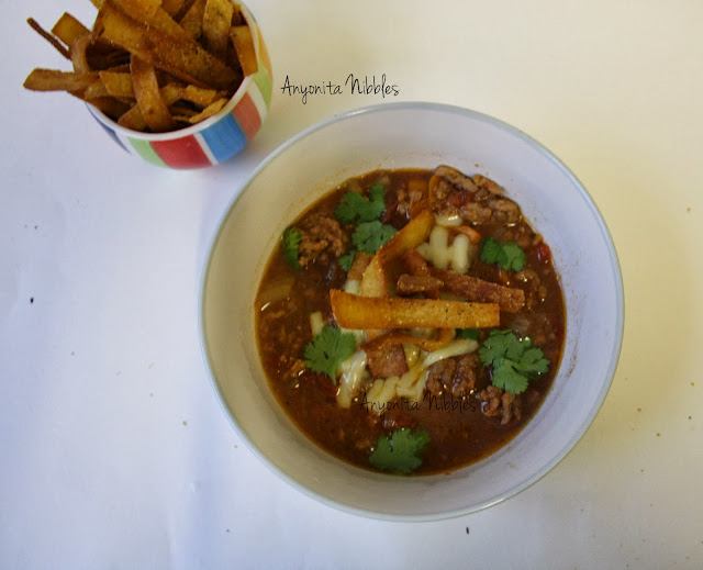 A bowl of crock pot beef tortilla soup with crispy tortilla strips from www.anyonita-nibbles.com