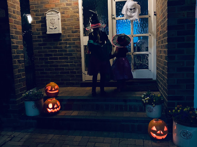 two children in witches outfits on a doorstep outside a closed front door with 3 pumpkins visible
