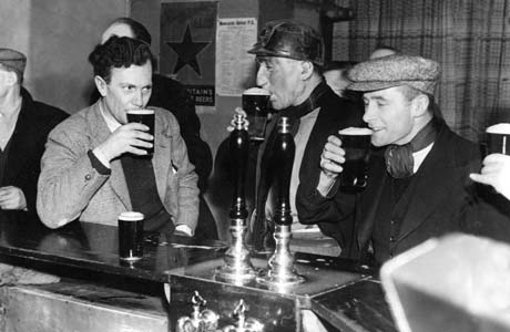 Old black and white photo of three men drinking bitter many years ago.