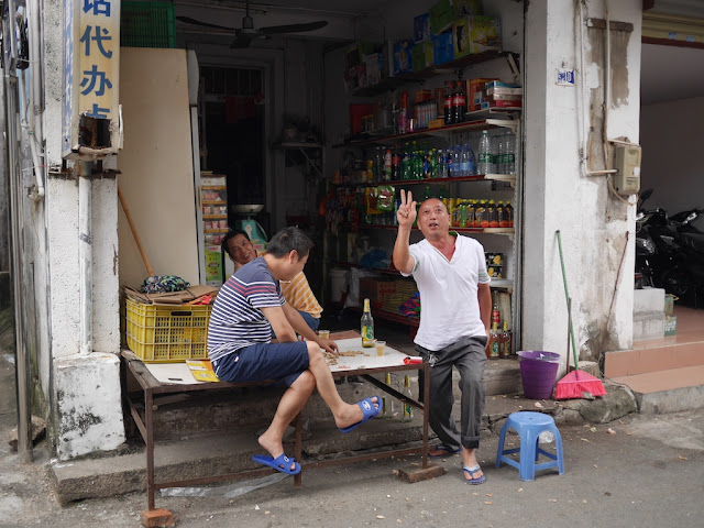 man posing for photo in front of a small convenience store