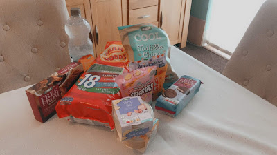 a pile of food including crisps, brownies, smarties and more