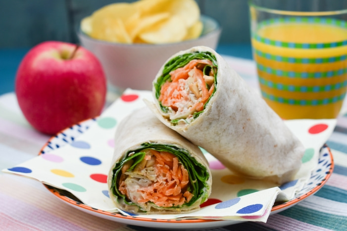 A Carrot and Spinach Crunch Lunch Wrap cut in half and served on a spotty napkin with an apple and crisps