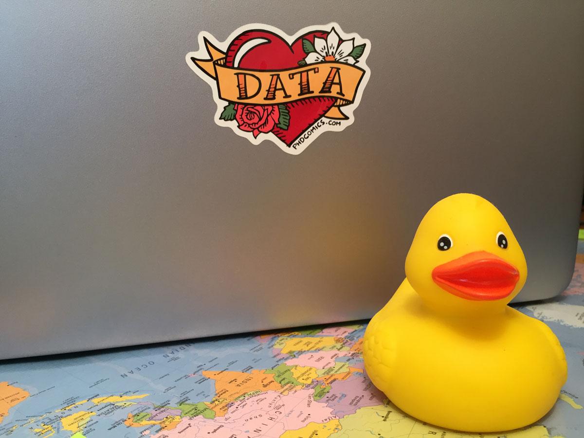 Läppärin kannessa on sydäntarra, jossa lukee DATA, sekä etualalla kumiankka.