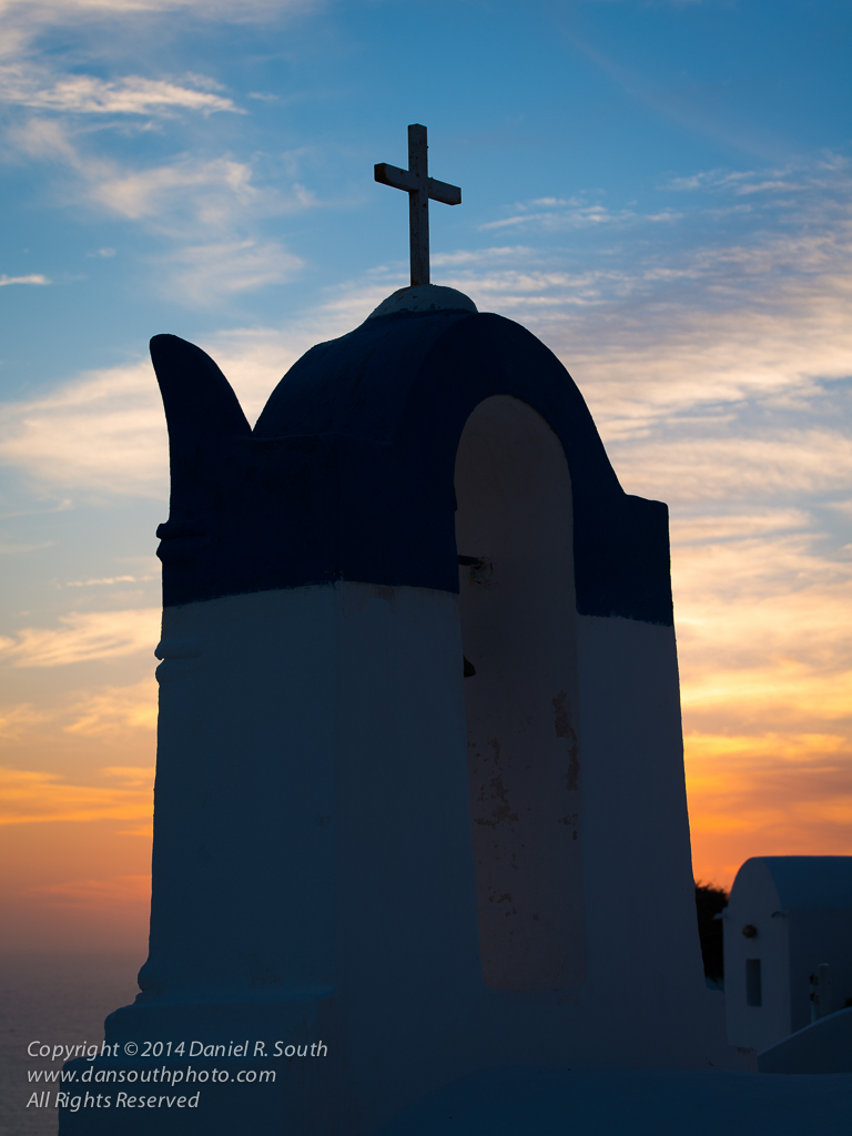 a photo of a chapel on santorini silhouette against the sunset