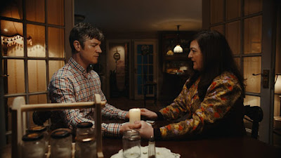 "Maeve Wiggins and Barry Ward hold hands and do a seance in a movie still for the 2019 horror comedy ""Extra Ordinary"""