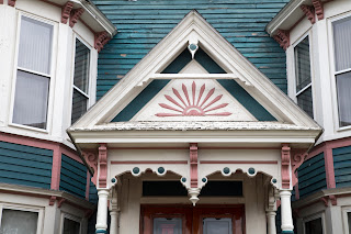 An architectural detail of an entryway to a peeling painted lady Victorian style home in Dover, New Hampshire