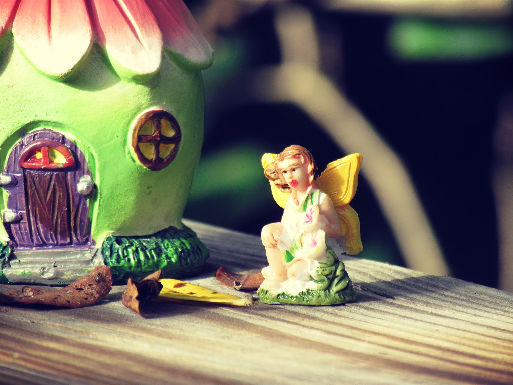 Fairy dollhouse in minty green with pink roofing and a fairy figurine sitting in mother earth