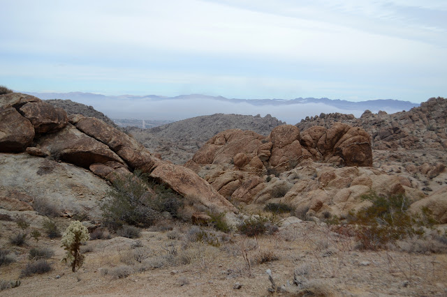 large rocks, small rocks, foggy city, and mountains