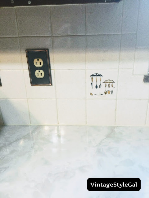 Utensils on accent tile in kitchen