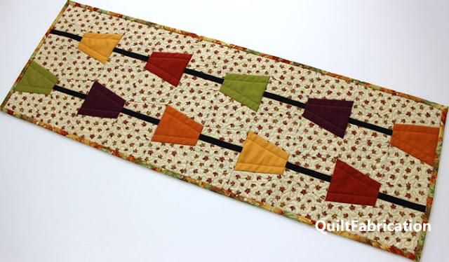 fall colored tumbler blocks on a leaf fabric