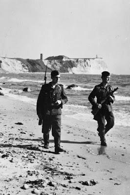 Zwei bewaffnete Soldaten in Uniform laufen den Sandstrand auf Rügen.