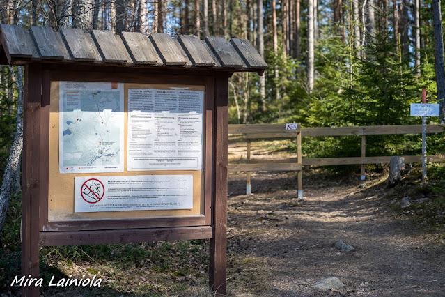 Opastaulu, jossa kartta ja pyöräilykieltomerkki, metsäpolun varrella