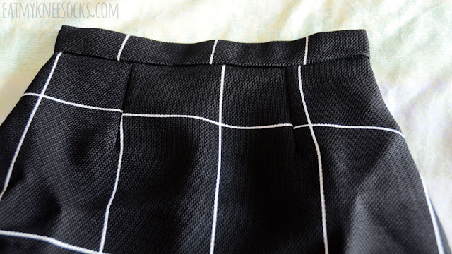 Details on the minimalist monorhome black grid print mini bodycon skirt from SheIn.