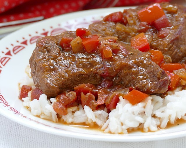 steak with rice on a white plate.