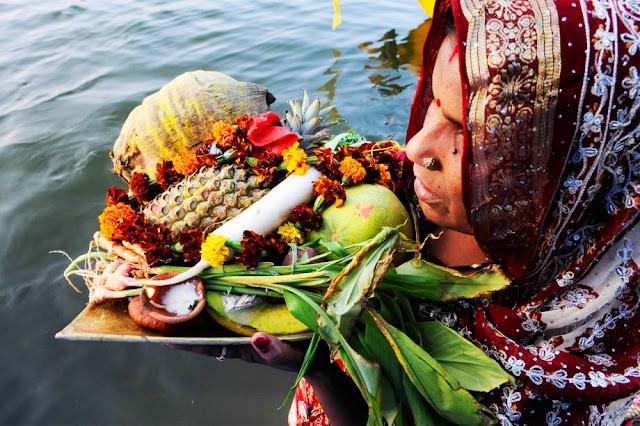 Devota hindu é vista com oferendas em adoração à divindade do sol 'Surya'