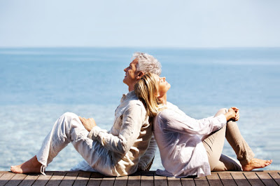 An older couple leaning against each other on a pier
