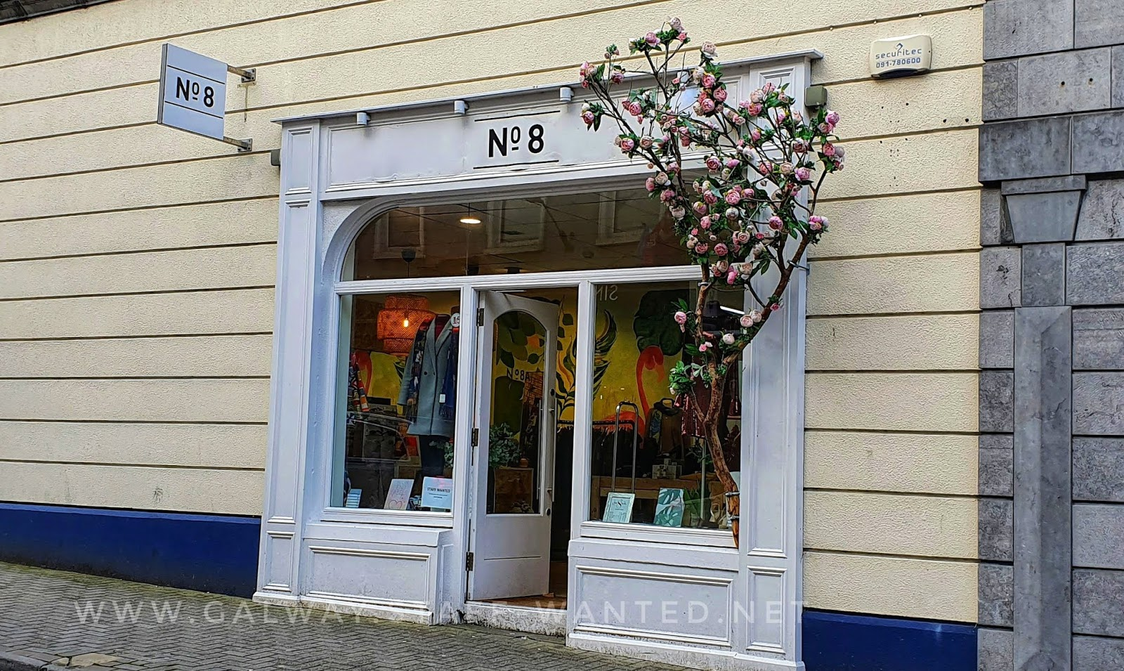 shopfront decorated with artificial branch of cherry blossom tree with pale pink flowers